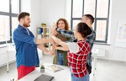 Szczęśliwa kreatywnie drużyna pokazuje aprobaty przy biurem fotografia stock