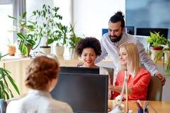 Szczęśliwa kreatywnie drużyna z komputerem w biurze Zdjęcia Royalty Free