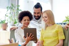Szczęśliwa kreatywnie drużyna z pastylka komputerem osobistym w biurze Obraz Royalty Free
