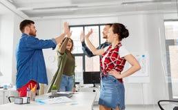 Szczęśliwa kreatywnie drużynowa robi wysokość pięć przy biurem zdjęcie stock
