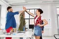 Szczęśliwa kreatywnie drużynowa robi wysokość pięć przy biurem fotografia royalty free