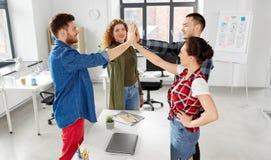 Szczęśliwa kreatywnie drużynowa robi wysokość pięć przy biurem zdjęcia royalty free
