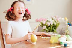 Szczęśliwa 7 lat dzieciaka dziewczyna maluje Easter jajka Wielkanocny rzemiosło i wakacyjni przygotowania Fotografia Royalty Free
