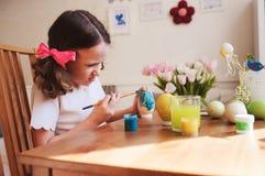 Szczęśliwa 7 lat dzieciaka dziewczyna maluje Easter jajka Wielkanocny rzemiosło i wakacyjni przygotowania Obrazy Royalty Free
