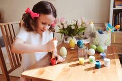Szczęśliwa 7 lat dzieciaka dziewczyna maluje Easter jajka Wielkanocny rzemiosło i wakacyjni przygotowania Fotografia Stock