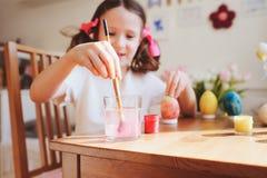 Szczęśliwa 7 lat dzieciaka dziewczyna maluje Easter jajka Wielkanocny rzemiosło i wakacyjni przygotowania Obraz Royalty Free