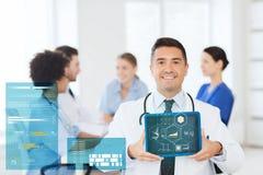 Szczęśliwa lekarka z pastylka komputerem osobistym nad drużyną przy kliniką Obrazy Royalty Free