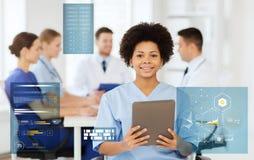 Szczęśliwa lekarka z pastylka komputerem osobistym nad drużyną przy kliniką Obraz Royalty Free