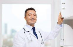Szczęśliwa lekarka z schowkiem w medycznym biurze obrazy stock