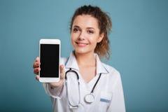 Szczęśliwa lekarka z stetoskopem pokazuje pustego smartphone ekran zdjęcia stock