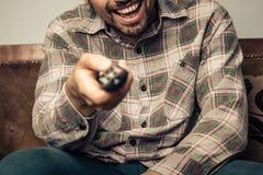 Szczęśliwa mężczyzna dopatrywania telewizja i odmienianie kanał zdjęcie royalty free