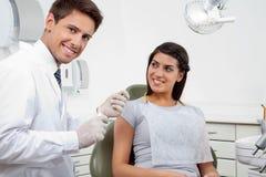 Szczęśliwa Męska dentysty mienia nić Podczas gdy pacjent Zdjęcia Stock