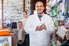 Szczęśliwa męska farmaceuty pozycja obok półek Zdjęcie Royalty Free