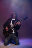 Szczęśliwa męska gitarzysta pozycja na kolanach i bawić się gitarze elektrycznej Zdjęcie Royalty Free