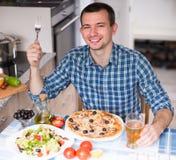Szczęśliwa męska obiadowa pizzy sałatka w kuchni Obraz Royalty Free