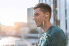 Szczęśliwa męska przesłuchanie piosenka w słuchawkach Fotografia Stock