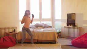 Szczęśliwa młoda ładna kobieta tanczy samotnie w pokoju z dużym okno w hełmofonach słucha muzyka na smartphone, dziewczyna spadki zbiory