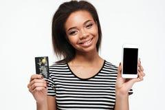 Szczęśliwa młoda afrykańska dama używa telefon i trzymający kartę debetową Fotografia Stock