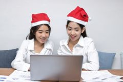 Szczęśliwa młoda Azjatycka biznesowa kobieta w Santa kapeluszach używać laptop w biurze Boże Narodzenia lub mas pojęcie Fotografia Royalty Free