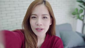 Szczęśliwa młoda Azjatycka kobieta bierze selfie i wideo wezwanie z smartphone w domu zbiory