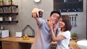 Szczęśliwa młoda Azjatycka para używa smartphone dla selfie w kuchni podczas gdy gotujący w domu Mężczyzna i kobieta przygotowywa zbiory