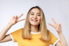 Szczęśliwa młoda azjatykcia kobieta pokazuje dwa zwycięstwo gesta z pustym copyspace terenem dla teksta lub palce, portret piękny obrazy royalty free