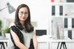Szczęśliwa młoda azjatykcia kobieta przy biurem Zdjęcie Stock