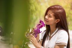 Szczęśliwa młoda azjatykcia kobiety mienia orchidea z szczęśliwym uśmiechem wewnątrz graden zdjęcia stock