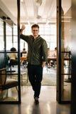 Szczęśliwa młoda biznesmen pozycja w biurowym drzwi Obrazy Stock