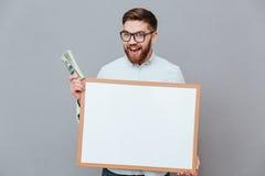 Szczęśliwa młoda biznesmena mienia copyspace deska i pieniądze Fotografia Royalty Free