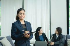 Szczęśliwa młoda biznesowa kobieta z jej personelem, ludzie grupy w tle przy nowożytnym jaskrawym biurem indoors obrazy stock