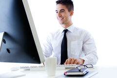 Szczęśliwa młoda biznesowego mężczyzna praca w nowożytnym biurze na komputerze Zdjęcie Royalty Free
