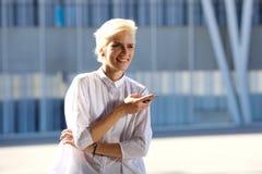 Szczęśliwa młoda blond kobieta z telefonem komórkowym Obrazy Royalty Free