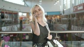 Szczęśliwa młoda blondynki kobieta używa telefon komórkowego przy centrum handlowym, piękny studencki dziewczyna zakupy w centrum zbiory