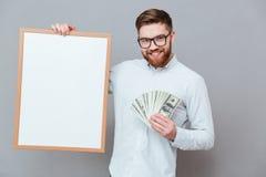 Szczęśliwa młoda brodata biznesmena mienia copyspace deska i pieniądze Obrazy Stock