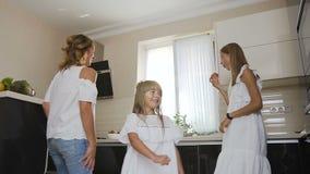 Szczęśliwa młoda caucasian rodzina tanczy wpólnie w kuchni w domu Mama z dwa córkami ubierać w bielu zbiory