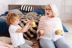 Szczęśliwa młoda chłopiec bawić się z jabłkiem Zdjęcia Royalty Free
