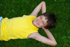 Szczęśliwa młoda chłopiec na trawie obraz royalty free