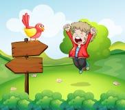 Szczęśliwa młoda chłopiec przed drewnianymi strzała Zdjęcia Royalty Free