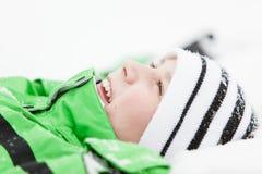 Szczęśliwa młoda chłopiec relaksuje w zima śniegu Fotografia Royalty Free