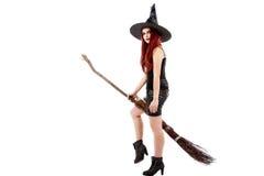 Szczęśliwa młoda czarownica z miotłą, odizolowywającą na białym pracownianym backgro Zdjęcia Royalty Free