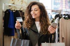 Szczęśliwa młoda dama trzyma kartę debetową z torba na zakupy Obrazy Royalty Free