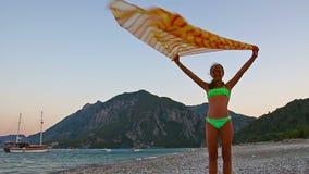 Szczęśliwa młoda dziewczyna bawić się z przesłoną w wiatrze na plaży zbiory