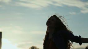 Szczęśliwa młoda dziewczyna cieszy się zmierzch w mieście Wirujący, trzymający up jego ręki Długi falisty włosy w wiatrze zbiory