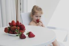 Szczęśliwa młoda dziewczyna je czerwone truskawki zdjęcie stock