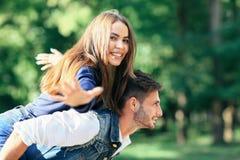 Szczęśliwa młoda dziewczyna na plecy przedstawia ptaka facet Fotografia Royalty Free