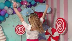 Szczęśliwa młoda dziewczyna rzuca up stubarwnego świecidełko przy przyjęciem swobodny ruch zbiory