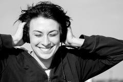 Szczęśliwa młoda dziewczyna słucha muzyka na ono uśmiecha się i dachu z hełmofonami Obrazy Stock