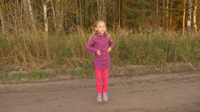 Szczęśliwa młoda dziewczyna tanczy outdoors Chirliderka trenuje przy rolnej drogi pogodnym wieczór Handheld zbiory