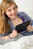 Szczęśliwa młoda dziewczyna używa cyfrową pastylkę Fotografia Royalty Free
